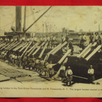 Unloading lumber in the Twin Cities, postcard (1906).jpg